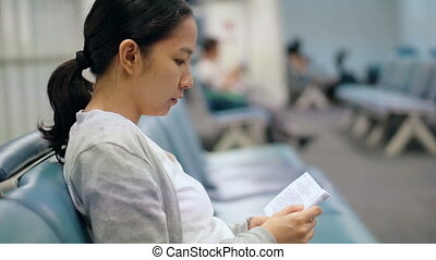 Asian woman reading book in airport