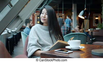 Beautiful Asian woman reading book relaxing sitting at table...