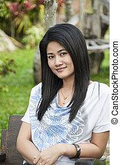 Beautiful Asian woman relax in park