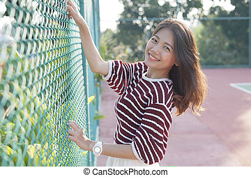 beautiful asian woman relaxing ,happiness vacation in tennis sport club