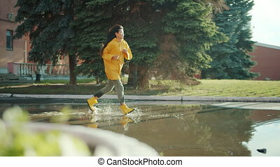 Beautiful Asian woman student is running in puddles wearing wet clothing raincoat and gumboots enjoying joyful activity. Youth, weather and people concept.