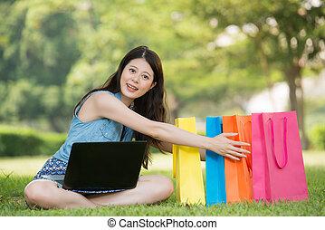 beautiful asian woman shopping online holding gift