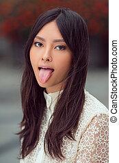 Beautiful asian woman showing tongue