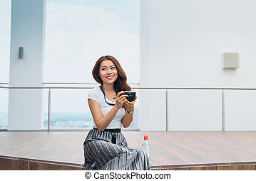 Beautiful asian woman sit at the edge of street, smiling with camera in hand, travel concept.