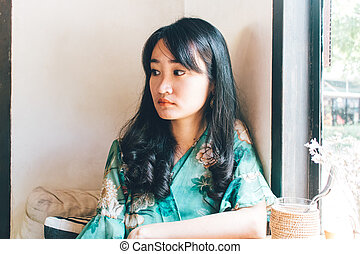 Beautiful Asian woman sitting in the cafe.