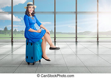 Beautiful asian woman sitting on suitcase while waiting for departure airplane