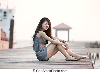beautiful asian woman sitting on wood pier with relaxing emotion and smiling to camera use for attractive woaman and people female topic