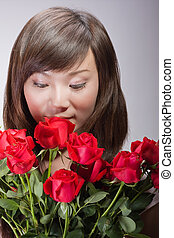 beautiful asian woman smelling flowers
