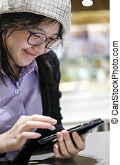 Beautiful asian woman smiling and using mobile phone