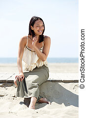 Beautiful asian woman smiling at the beach