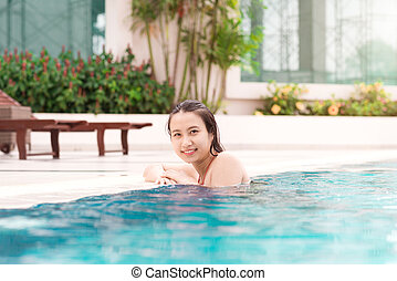Beautiful asian woman smiling in a swimming pool