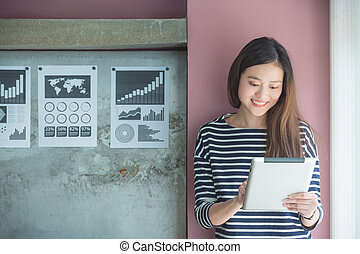 Beautiful asian woman smiling while using tablet computer