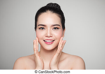 Beautiful asian woman touching and enjoy her face skin.