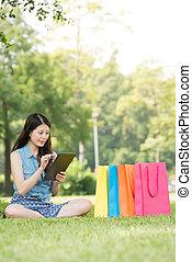 beautiful asian woman using digital tablet shopping online