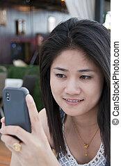 Beautiful Asian woman using phone.