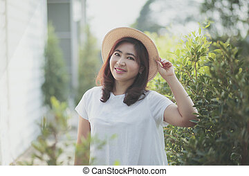 beautiful asian woman wearing straw hat with smiling face standing in garden