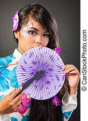 Beautiful asian woman wears a national dress is holding a fan