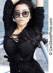 Beautiful asian woman with long hair in sunglasses poses near water