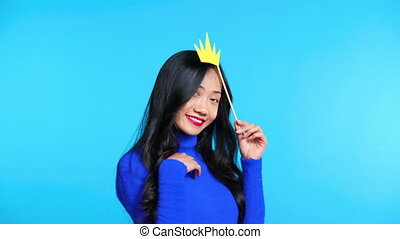 Beautiful asian woman with paper crown on stick send air ...
