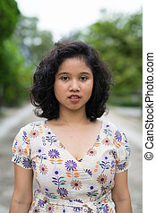 Beautiful Asian woman with short curly hair outdoors