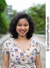 Beautiful Asian woman with short curly hair smiling outdoors