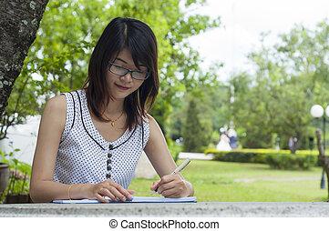 Beautiful Asian woman writing in park.