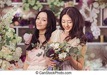 Beautiful asian women florists happy working in flower store with a lot of spring flowers