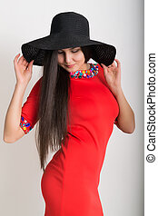 Beautiful asian young brunette in a little red dress and big black hat, standing and posing