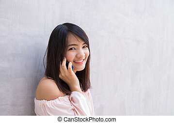 Beautiful asian young woman talking on Mobile Phone, over concrete wall