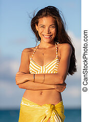 Beautiful Asian young woman wearing yellow bikini smiling candidly happy on summer travel beach vacation. Healthy smile portrait outside.