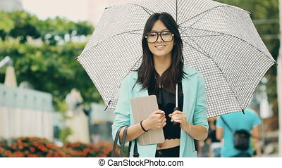 Beautiful asian young woman with tablet in city street