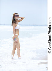 beautiful asian younger woman wearing beach bikini standing on sea beach