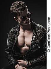 Beautiful athletic bodybuilder male model posing in studio. Expression on camera. Brutal man in leather suit.
