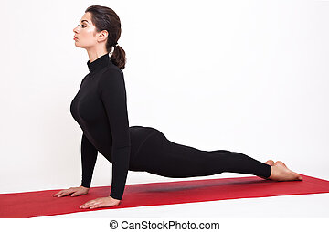 Beautiful athletic girl in black suit doing yoga. Urdhva Mukha Svanasana asanas - dogs pose muzzle up. Isolated on white background.