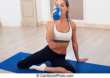 Beautiful athletic sporty woman sitting on yoga mat after some exercises drinks protein shake