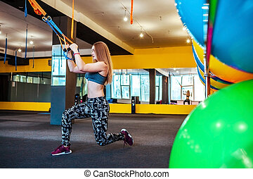 Beautiful athletic woman doing exercises using trx in sportswear at gym