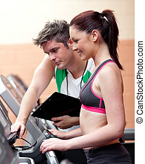 Beautiful athletic woman standing on a running machine with her personal coach in a fitness center