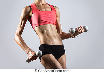 Beautiful athletic woman sweating while lifting dumbbells. Close-up of torso