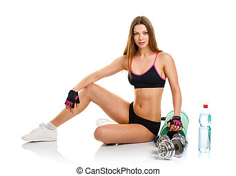 Beautiful athletic woman with dumbbells, mat for fitness, a bott
