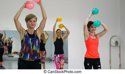 Beautiful athletic women at the gym in aerobics session with balls in hands