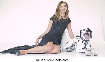 beautiful attractive girl in a black dress with a Dalmatian...