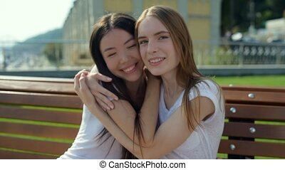 Positive emotions. Beautiful attractive young girls hugging each other and expressing cheer while sitting against nature background