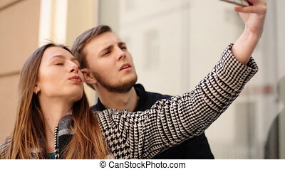 Beautiful attractive smiling woman taking selfies with her handsome boyfriend on her phone.