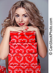 Beautiful attractive woman with red gift box on gray background