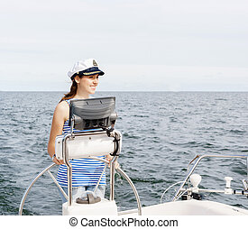 Beautiful, attractive young girl pilots a boat Mediterranean...