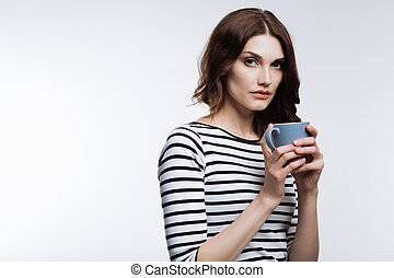 Beautiful auburn-haired woman holding a cup of coffee