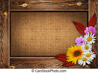 Beautiful autumn background with wooden frame and flowers on can