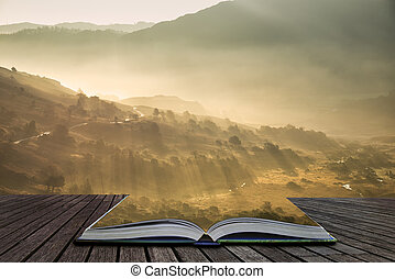 Beautiful Autumn Fall landscape sunrise in the Lake District with sun rays streaming through the fog into The Langdales valley coming out of pages of open story book