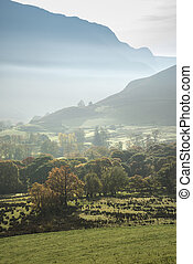 Beautiful Autumn Fall sunrise foggy landscape image over countryside in Lake District in England