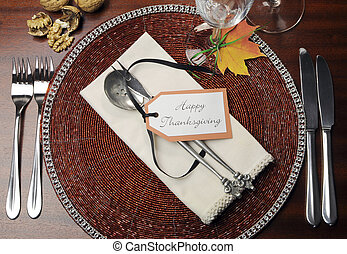 Beautiful Autumn Fall theme Thanksgiving dinner table place setting with Happy Thanksgiving tag attached to silverware. Aerial view with walnuts.